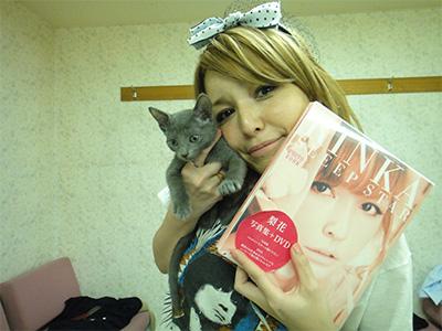 愛猫と雑誌を抱える梨花